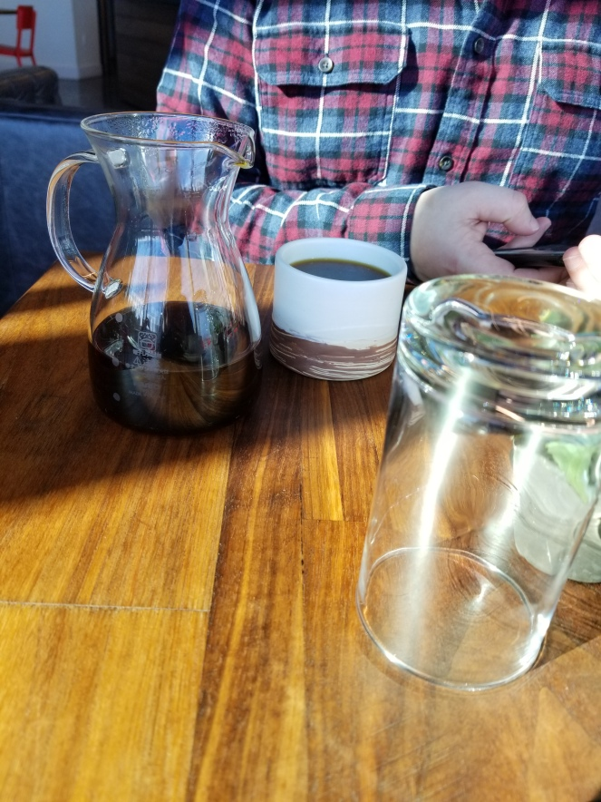 Image of a carafe of coffee, two tone coffee cup, an arm, and an upside down water glass.