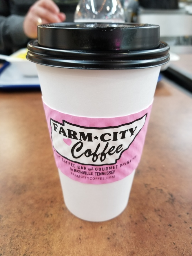 image of a to-go coffee cup with a pink logo saying Farm City Coffee.