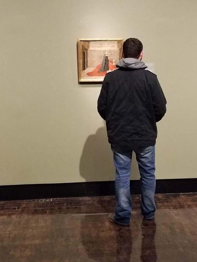 image of a man turned away from the camera viewing a painting.