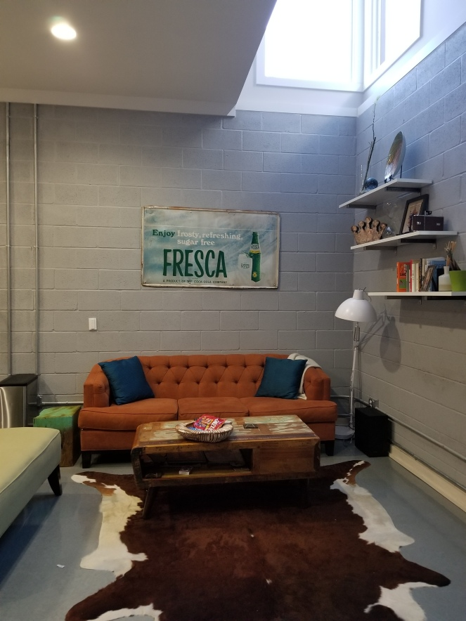 An image of an orange couch, cow skin rug, and Fresca advert.