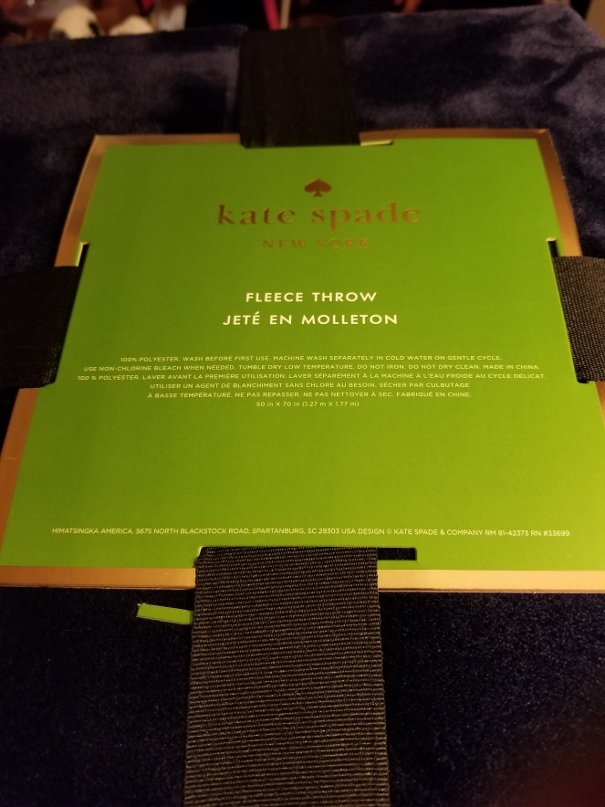 An image of the tag for a navy blue Kate Spade throw.