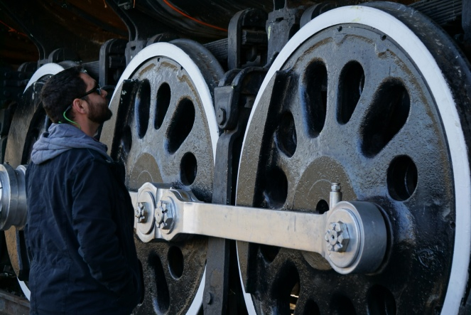 A man standing next to a train engine, looking up.