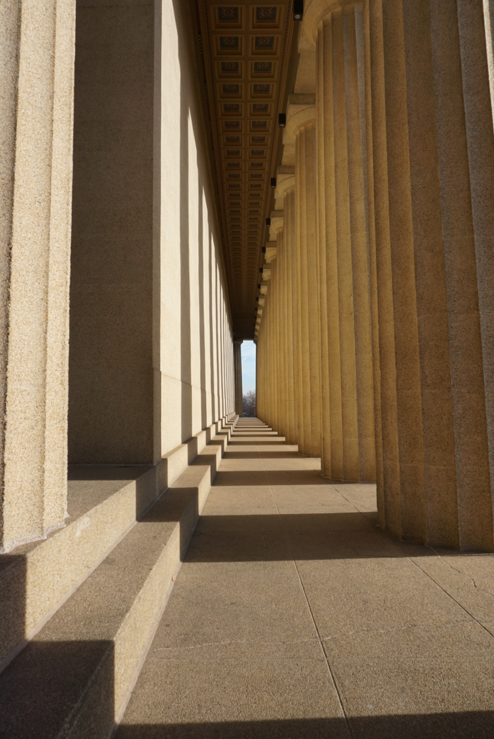 An image on the side of the Parthenon with the sun making a pattern between columns.