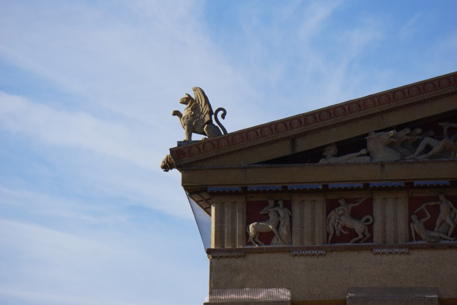 An image of a lion style gargoyle against a blue sky.